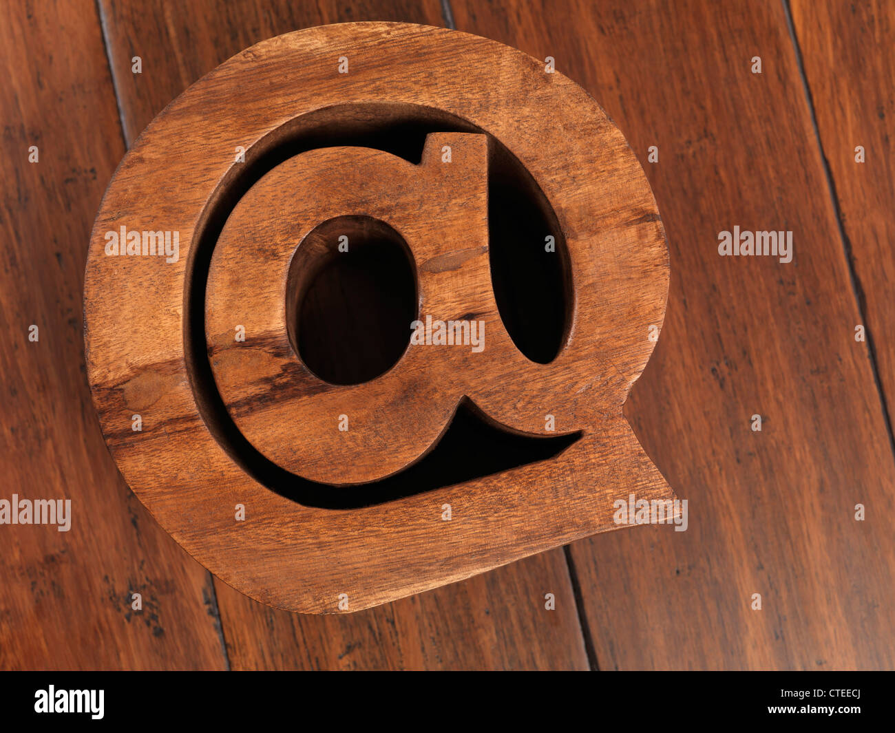 Internet and email symbol AT made of wood on hardwood floor background - Stock Image