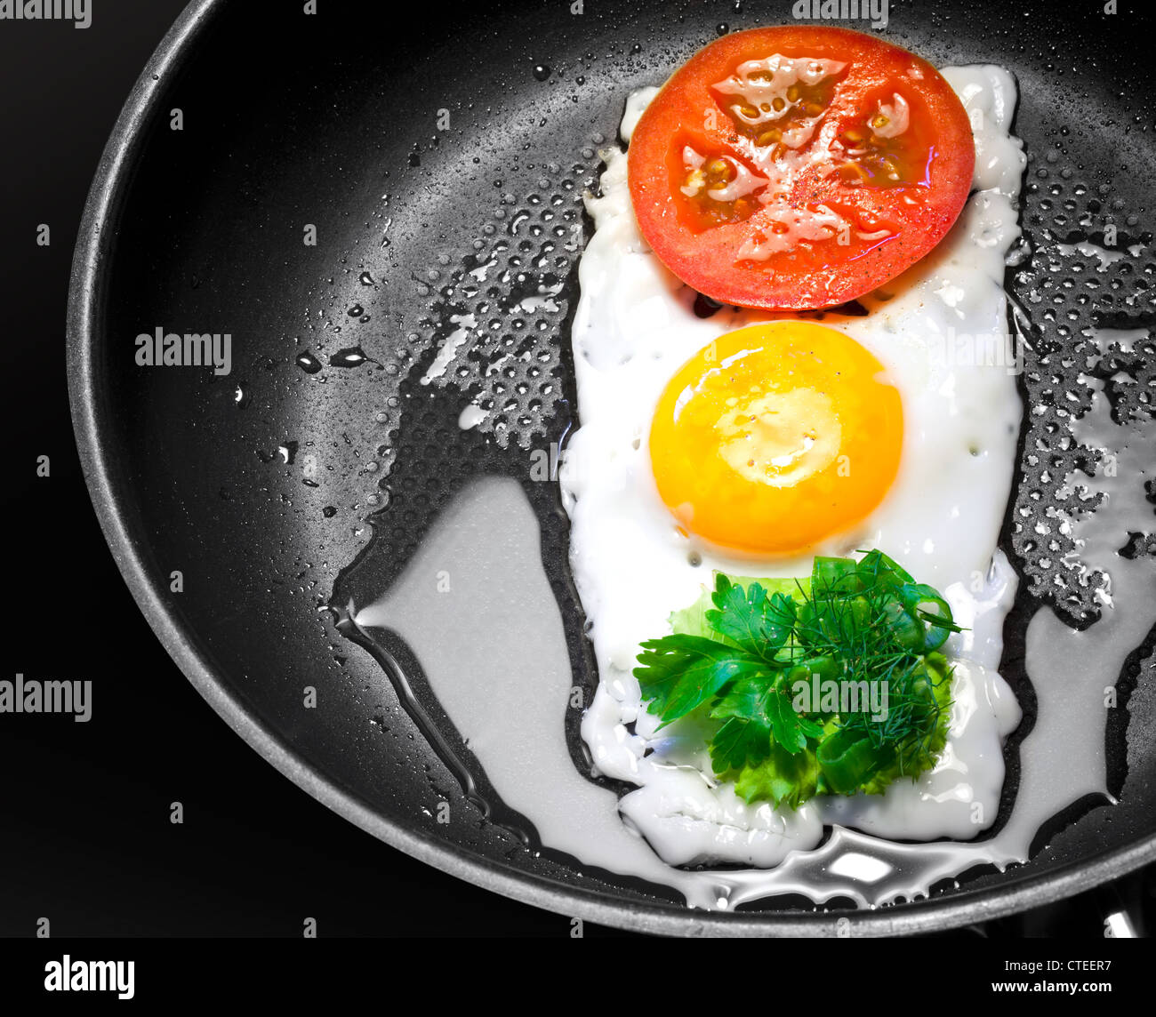 Original breakfast theme. Fried egg with tomato and greens in shape of Traffic Light in a frying pan - Stock Image