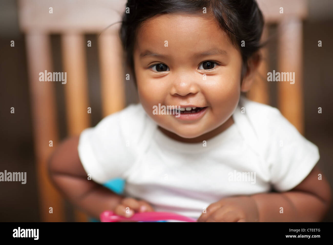 excited baby girl holding a spoon and sitting on a booster seat - Stock Image