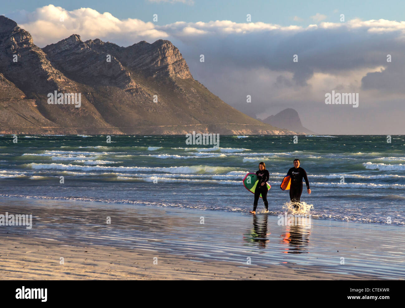 Two surfers in wet suits emerge from the ocean  - The Strand, Western Cape, South Africa - Stock Image