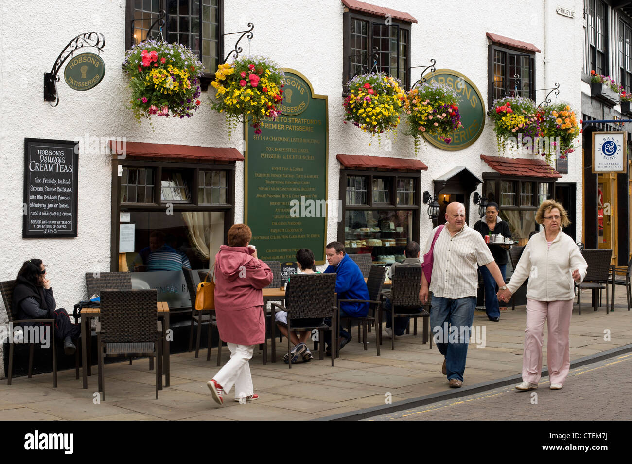hanging baskets, people sitting outside a cafe and visitors in Henley Street, Stratford upon Avon, Warwickshire. - Stock Image
