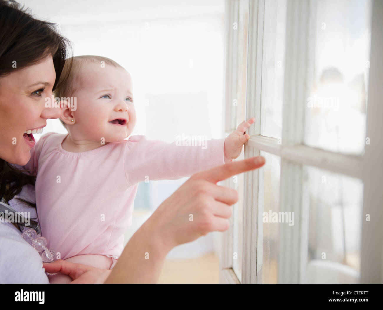 USA, New Jersey, Jersey City, Mother with baby daughter (6-11 months) looking through window - Stock Image