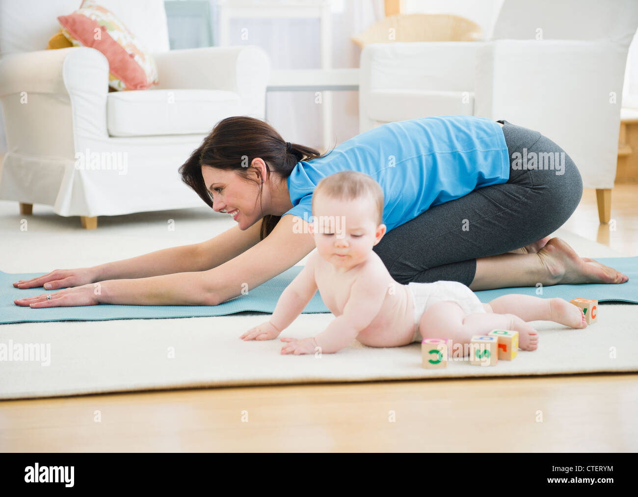 USA, New Jersey, Jersey City, Mother with baby daughter (6-11 months) practicing yoga - Stock Image