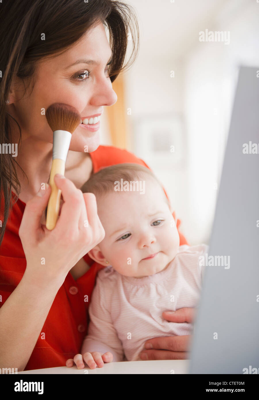 USA, New Jersey, Jersey City, Mother with baby daughter (6-11 months) doing make up - Stock Image