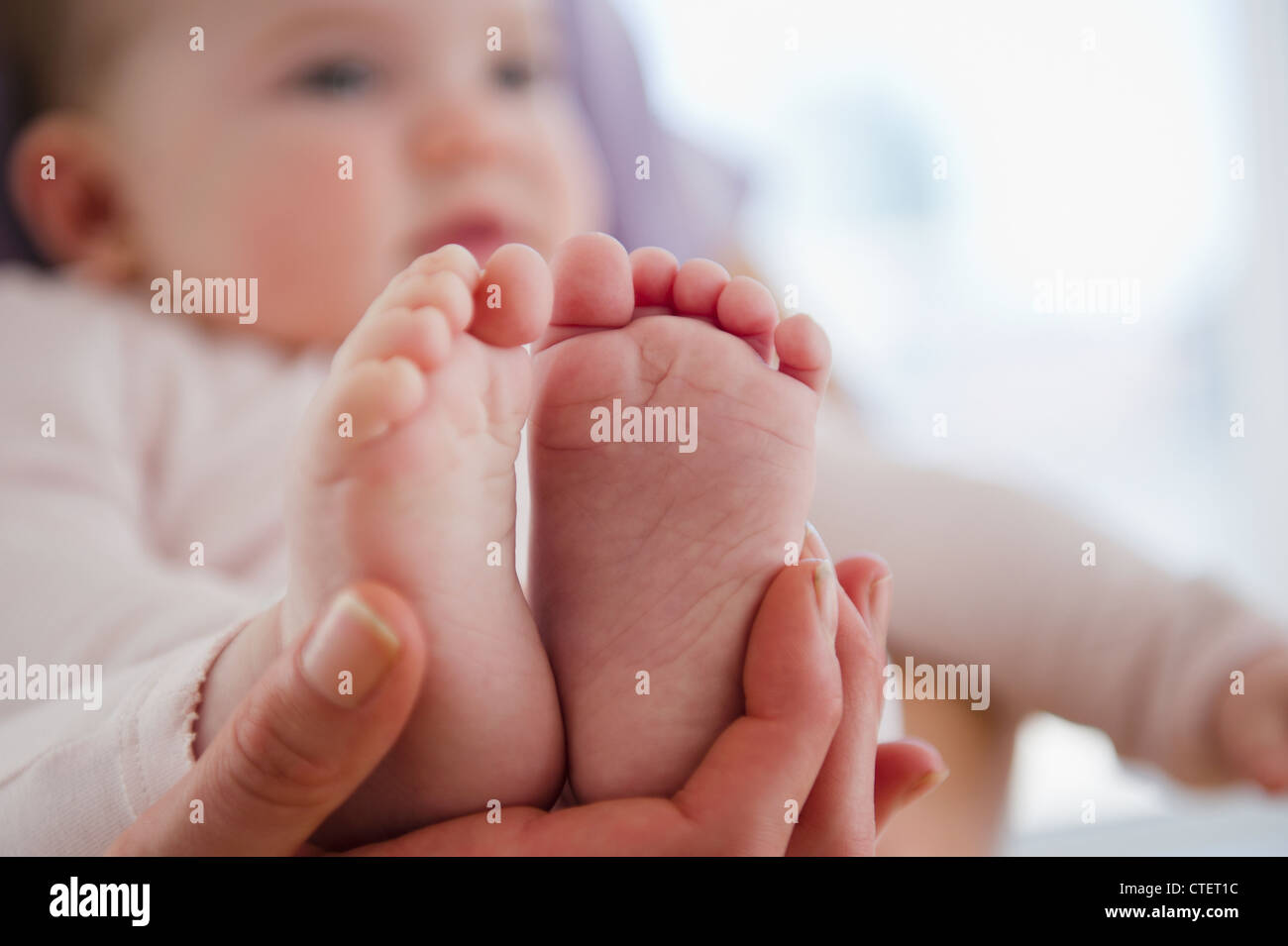 USA, New Jersey, Jersey City, Close up of mother's hand holding baby daughter's (6-11 months) feet Stock Photo