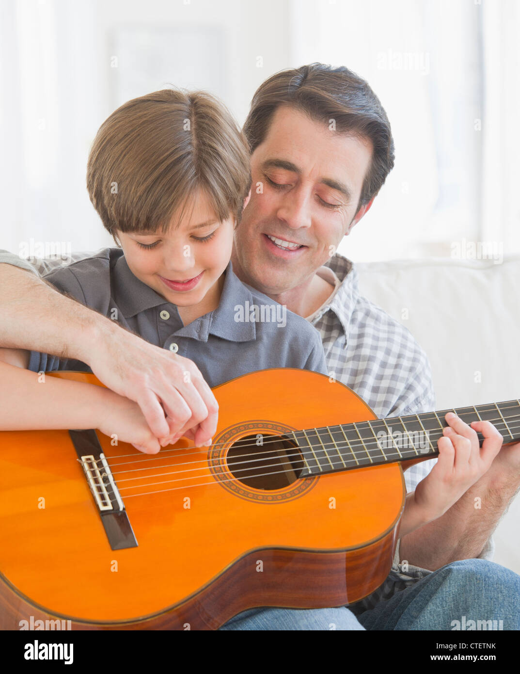 USA, New Jersey, Jersey City, Father teaching son (10-11 years) how to play acoustic guitar - Stock Image