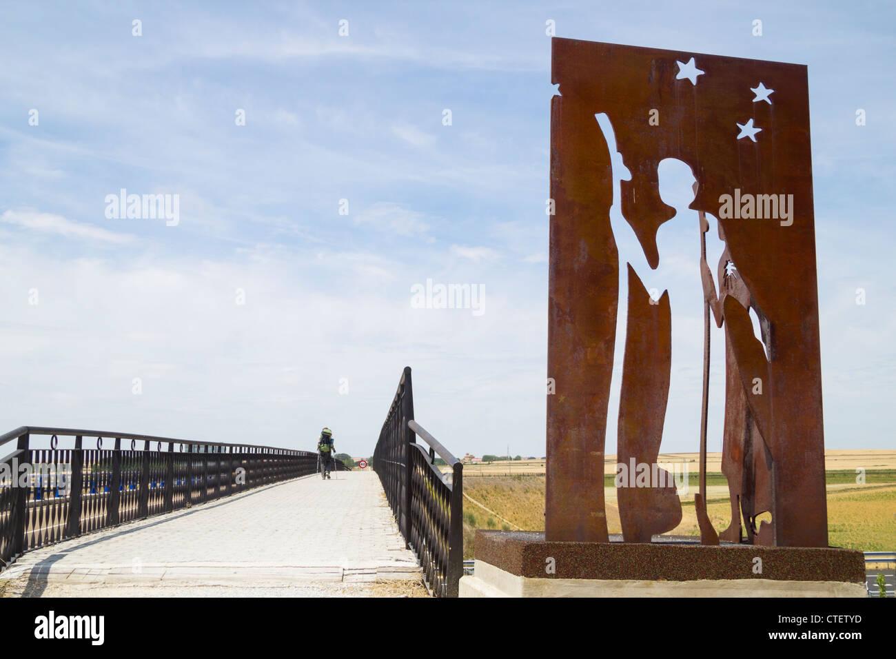 Pilgrim walking Camino de Santiago near metal Camino de Santiago sculpture in Fromista, Palencia province, Spain - Stock Image