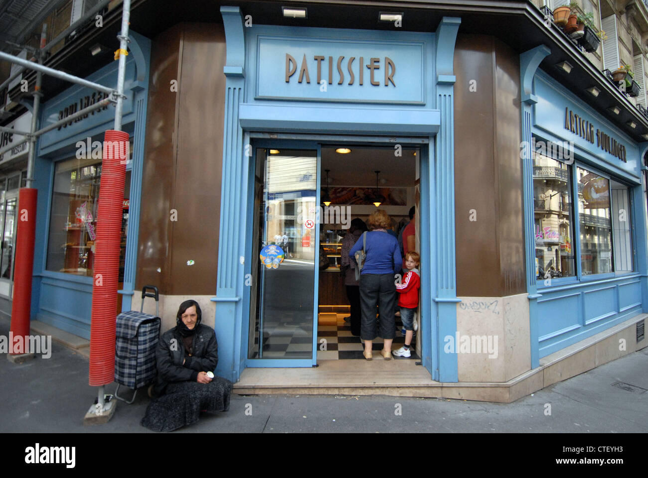A  beggar sits outside of a traditional bakery in the 9th Arrondissement  of Paris - Stock Image