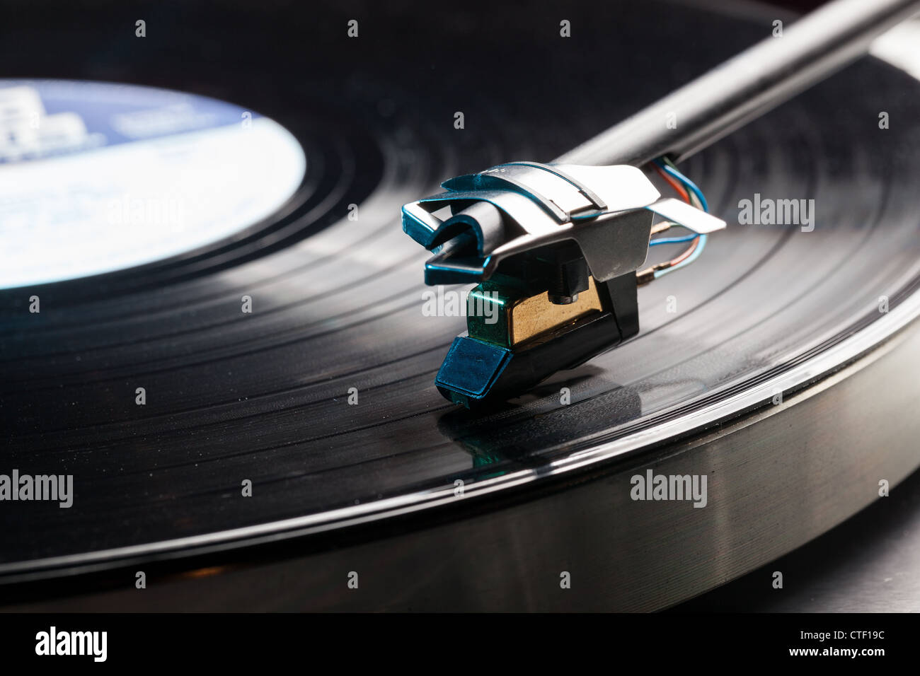Playing a vinyl record on a record player - LP record on a retro turntable  with tone arm and cartridge - Stock Image