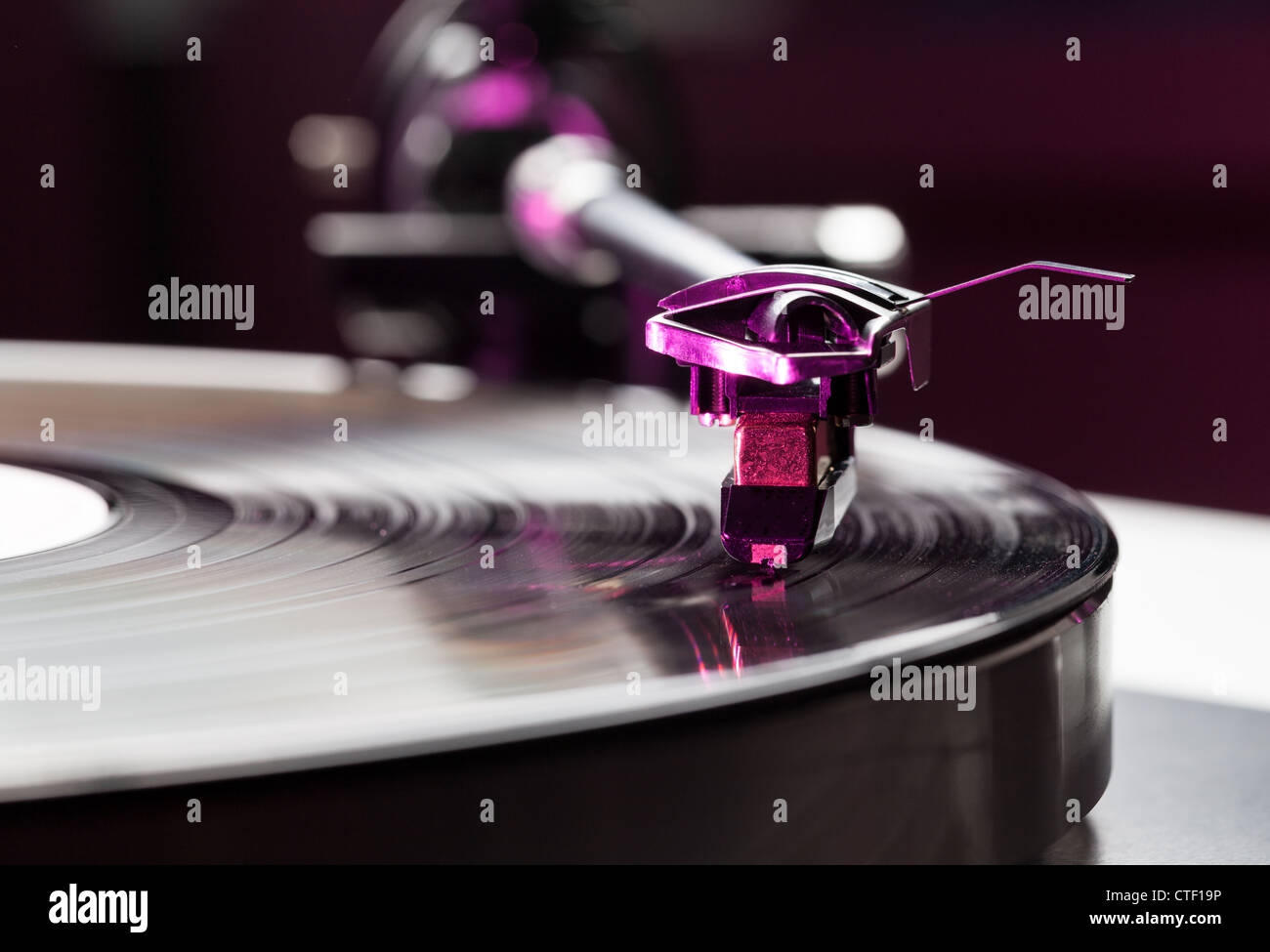 LP record on retro record player turntable with tone arm and cartridge - Stock Image
