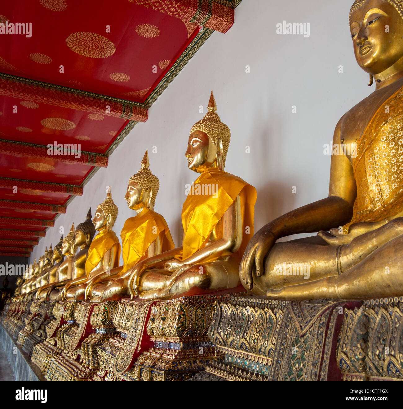 Row of golden buddha statues in Wat Po temple near Bangkok, Thailand - Stock Image