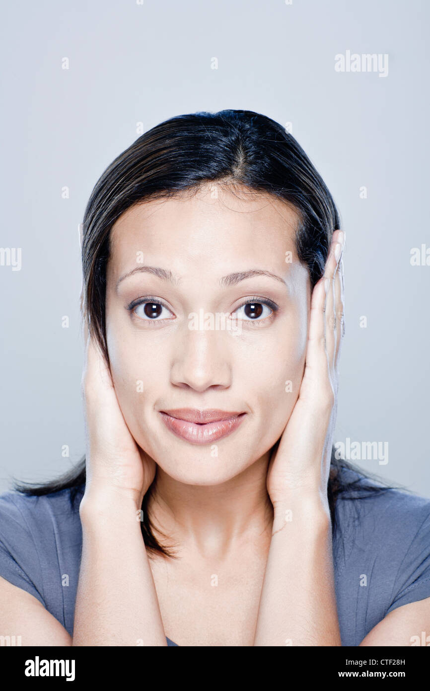 Portrait of young woman with hands covering ears, studio shot - Stock Image