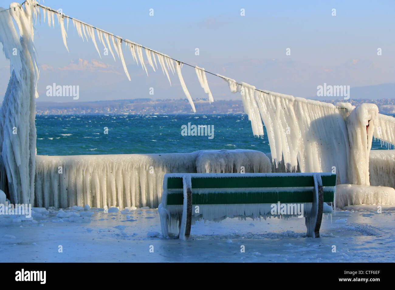 Frozen bench because of cold winter temperature and waves at Nyon, Switzerland - Stock Image