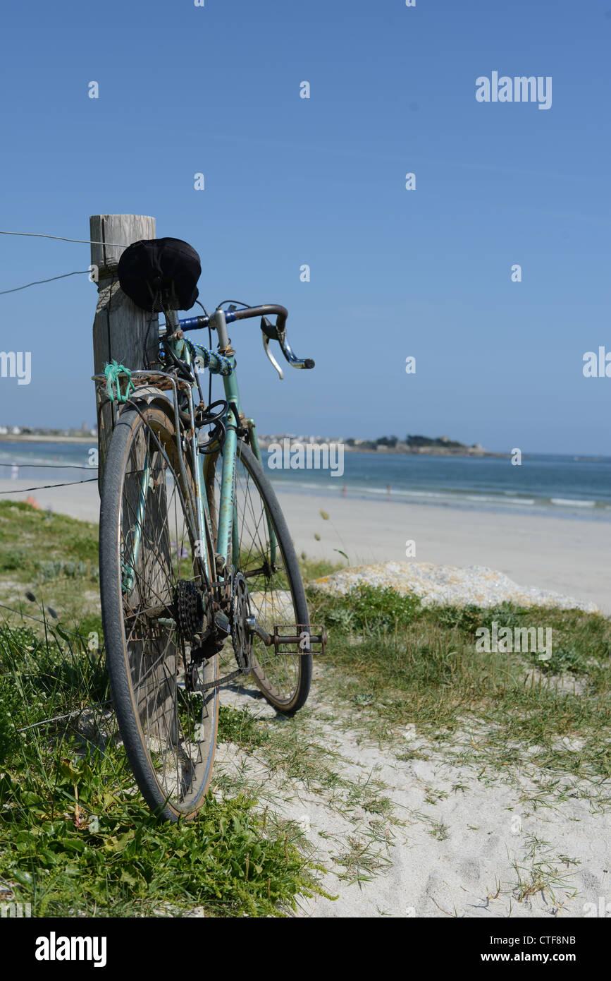 Bicycle at the beach Abgestelltes Fahrrad an einem Dünenweg in der Bretagne.  Zaun, Dünenschutz, Meer, Strandzugang Stock Photo