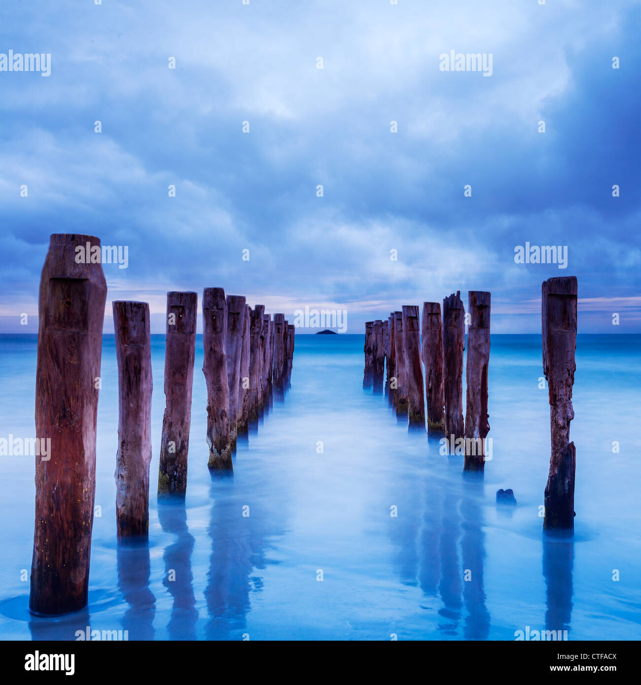 Storm clouds gather over old jetty posts. - Stock Image