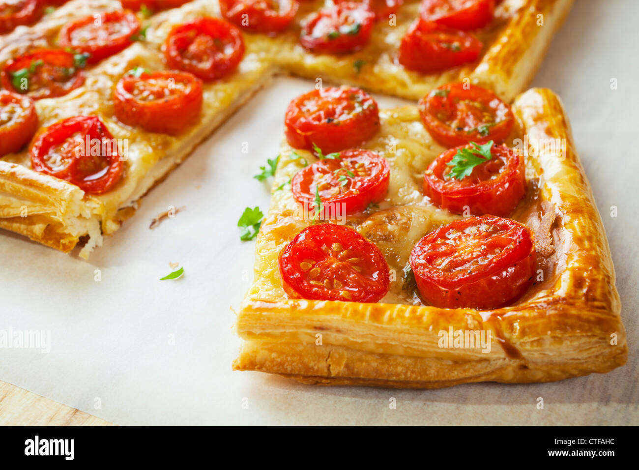 Tomato tart, puff pastry topped with mustard, cheese and cherry toamtoes. - Stock Image