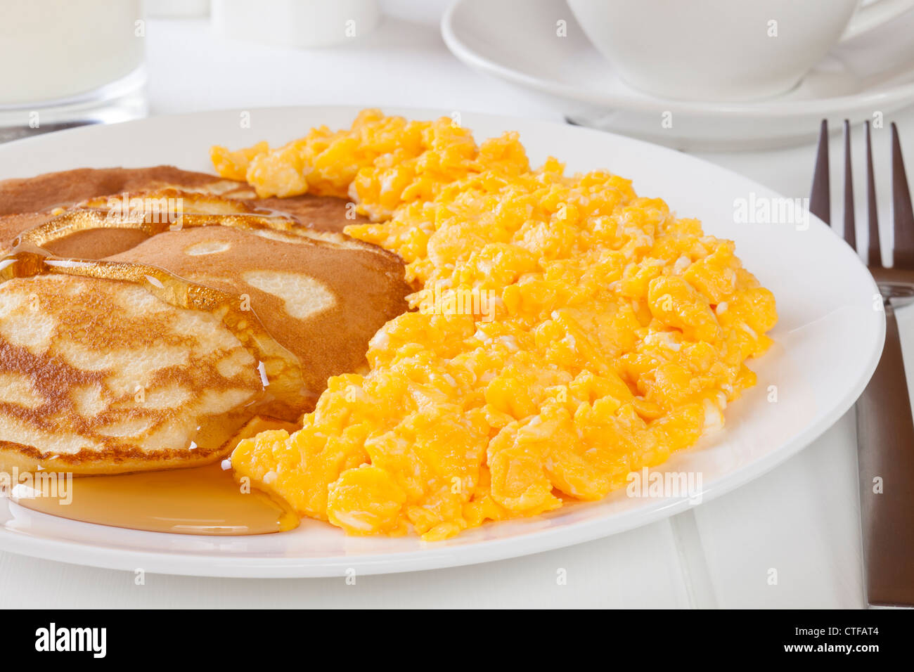 Homemade hotcakes with maple syrup, served with scrambled egg. - Stock Image