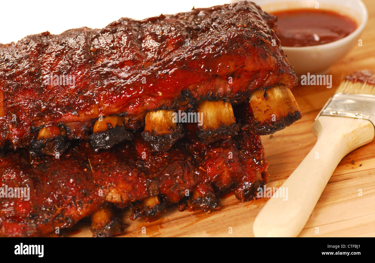 Two slabs of delicious BBQ spare ribs with dipping sauce - Stock Image