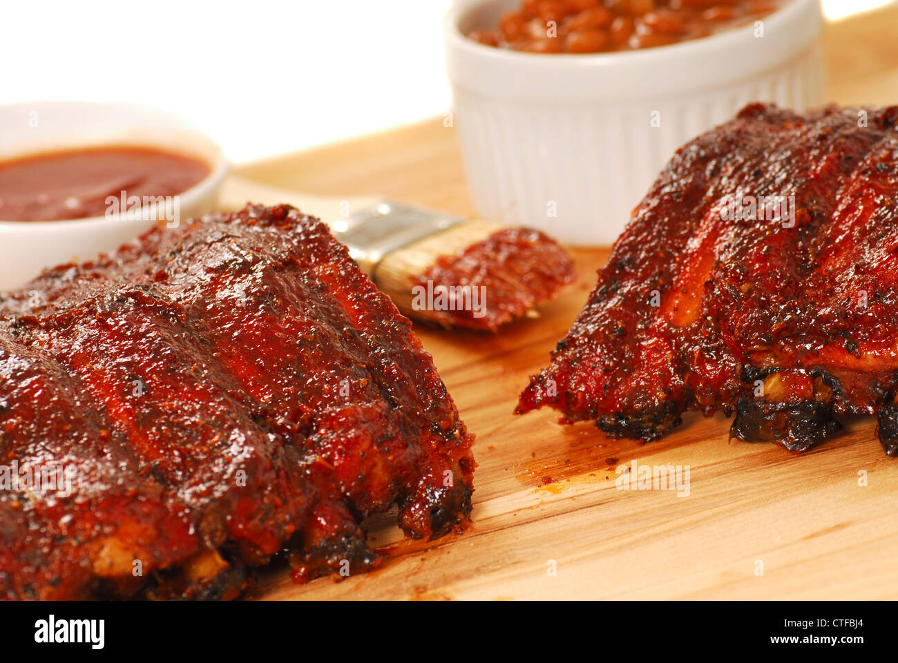 Slab of BBQ spare ribs with beans and dipping sauce - Stock Image