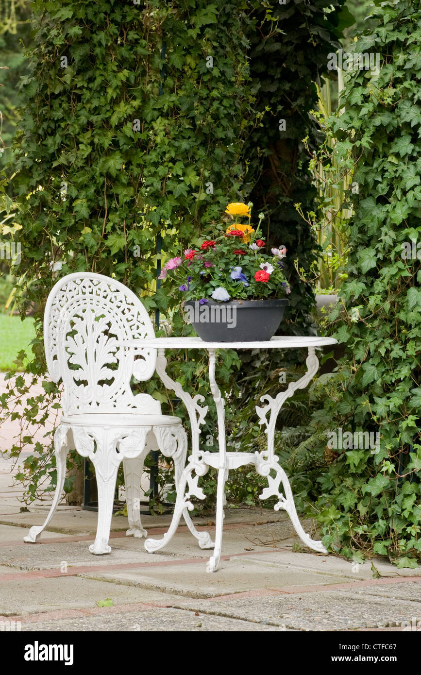 A White Wrought Iron Table And Chair Sit In A Garden Setting