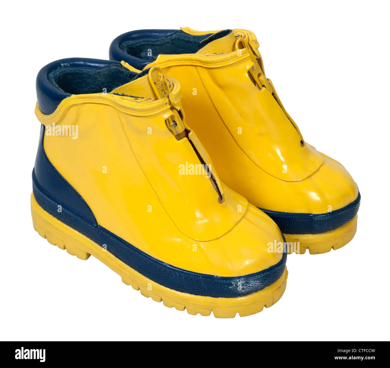 Yellow rubber boots to be worn on the feet to keep them dry - path included - Stock Image