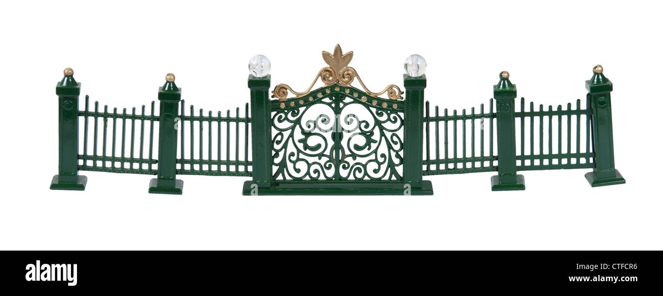 Metal fence with scrollwork painted green with gate entrance - path included - Stock Image