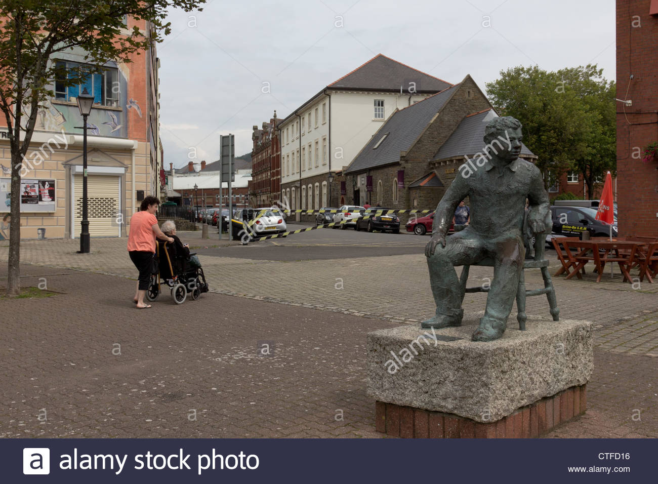 Lady pushes a woman in wheelchair past the John Doubleday statue of Dylan Thomas, Swansea. - Stock Image
