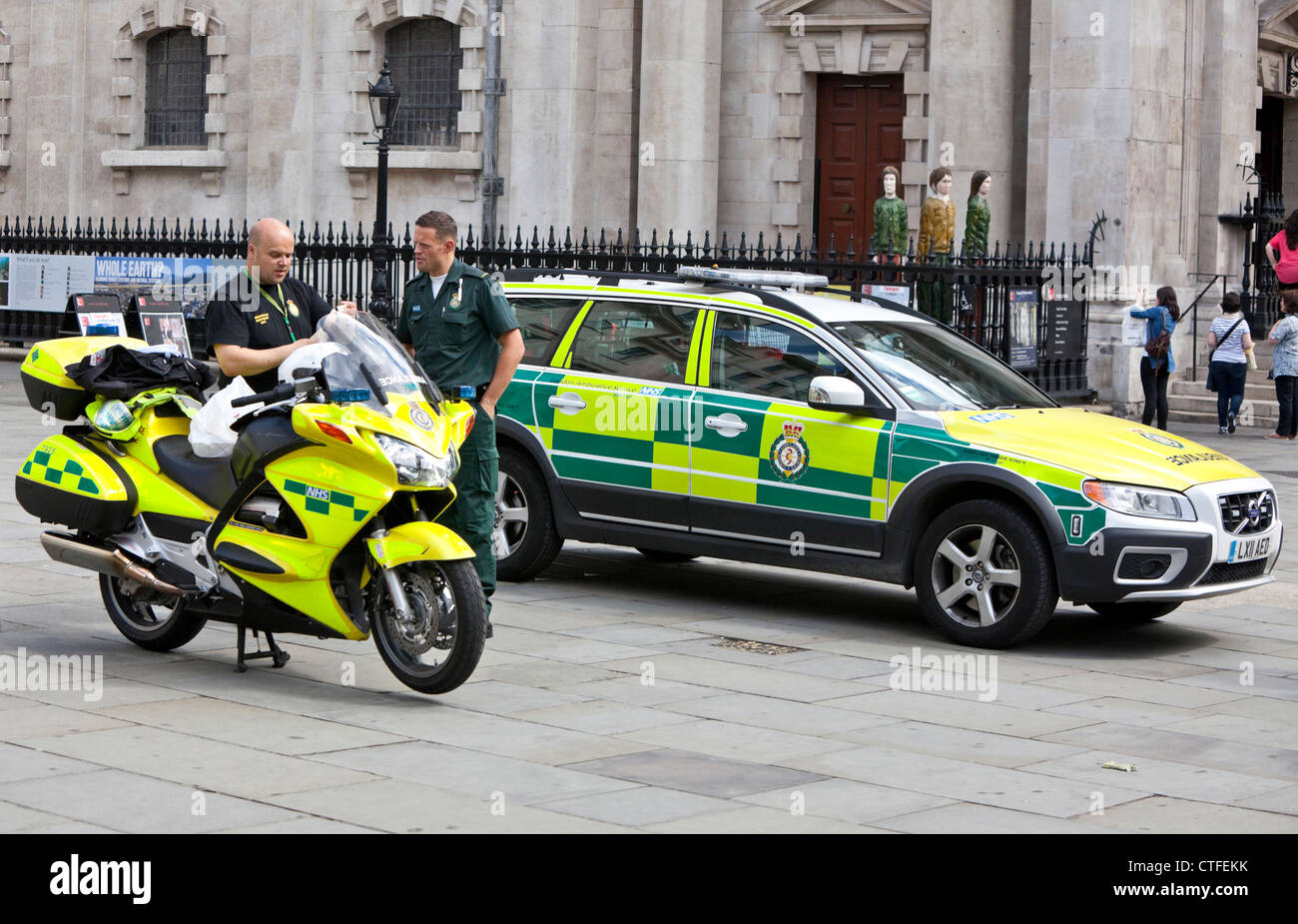 NHS ambulance and motorcycle parked outside St Martin's in the Fields Church, London, England, UK - Stock Image
