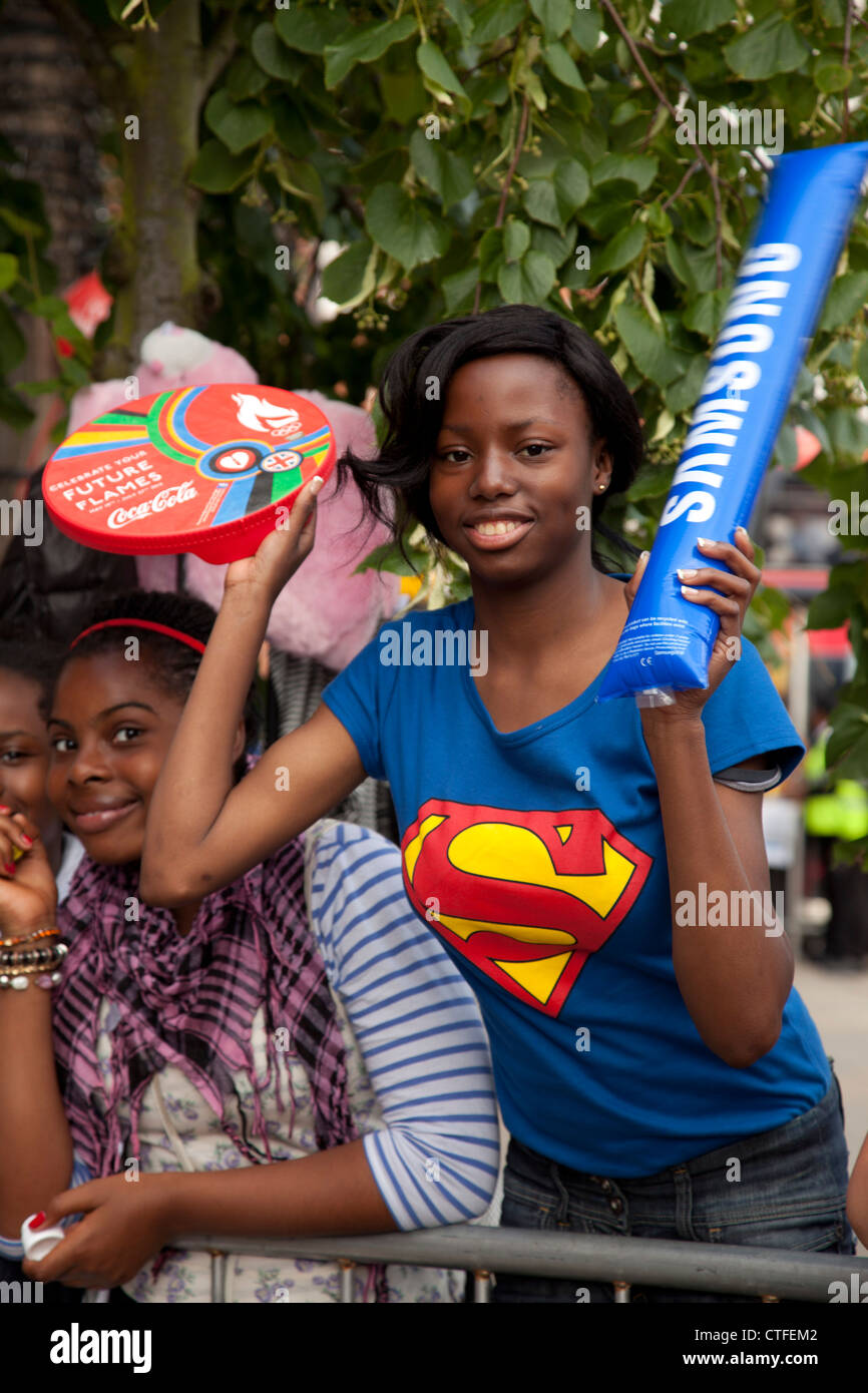 Children and young people with gifts from sponsors wait for London 2012 Olympic torch in Hackney, UK - Stock Image