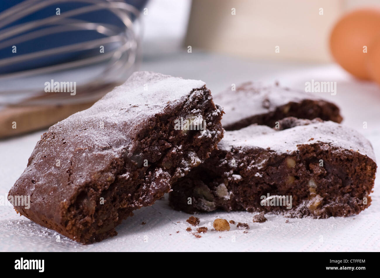 Pecan, Rum and Stem Ginger Chocolate Brownies dusted with icing sugar - Stock Image
