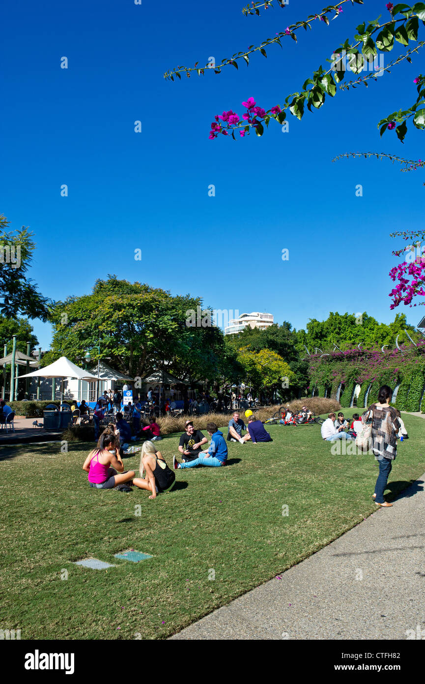 People relaxing in the sunshine on South Bank in Brisbane in Queensland in Australia. - Stock Image