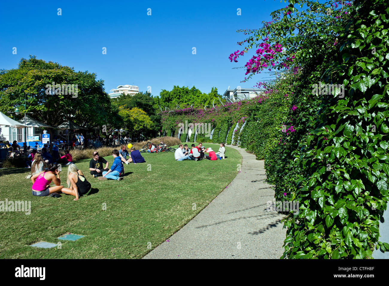 People relaxing in the sunshine on South Bank in Brisbane in Queensland Australia - Stock Image