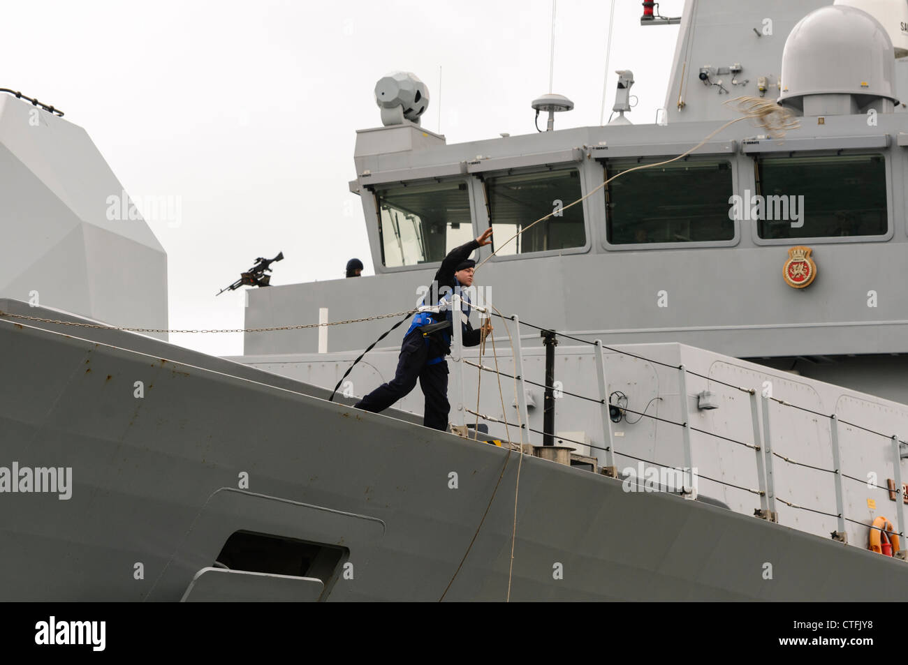 Sailor on Royal Navy Type 45 destroyer HMS Dragon throws a lead rope to dockers Stock Photo