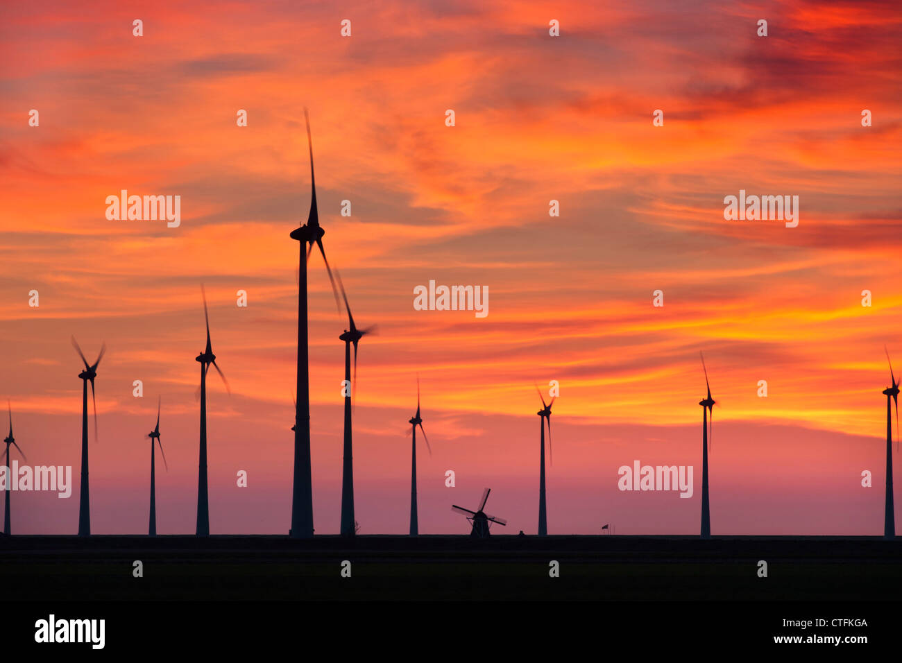 The Netherlands, Eemsmond, Eemshaven, Windturbines and traditional windmill. Sunset. - Stock Image