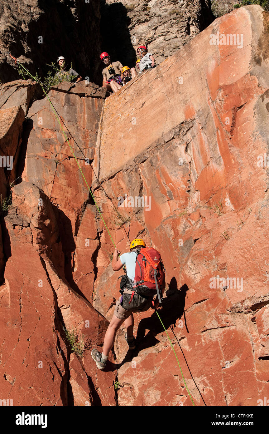 Hiker rappels the fourth rap waterfall in Benson Canyon, Dixie National Forest, Utah. - Stock Image