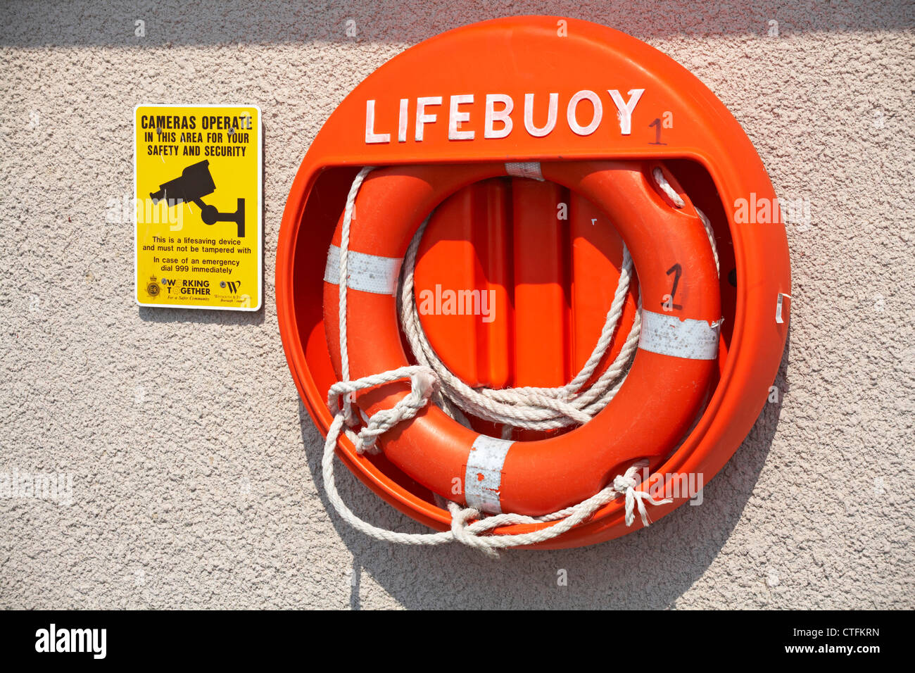 Lifebuoy ring with notice alongside advising cameras operate in the area at Weymouth in May - Stock Image