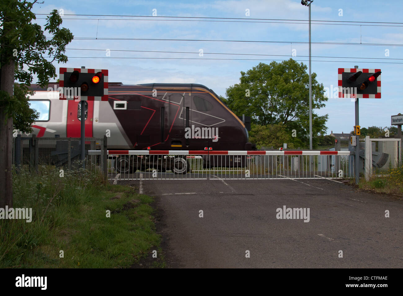 Rear of Cross Country Train at Level Crossing on the East Coast Mainline in North East England - Stock Image