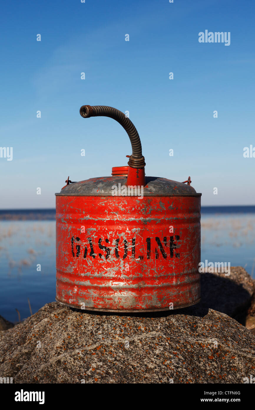 An old gasoline can sitting on a rock. - Stock Image