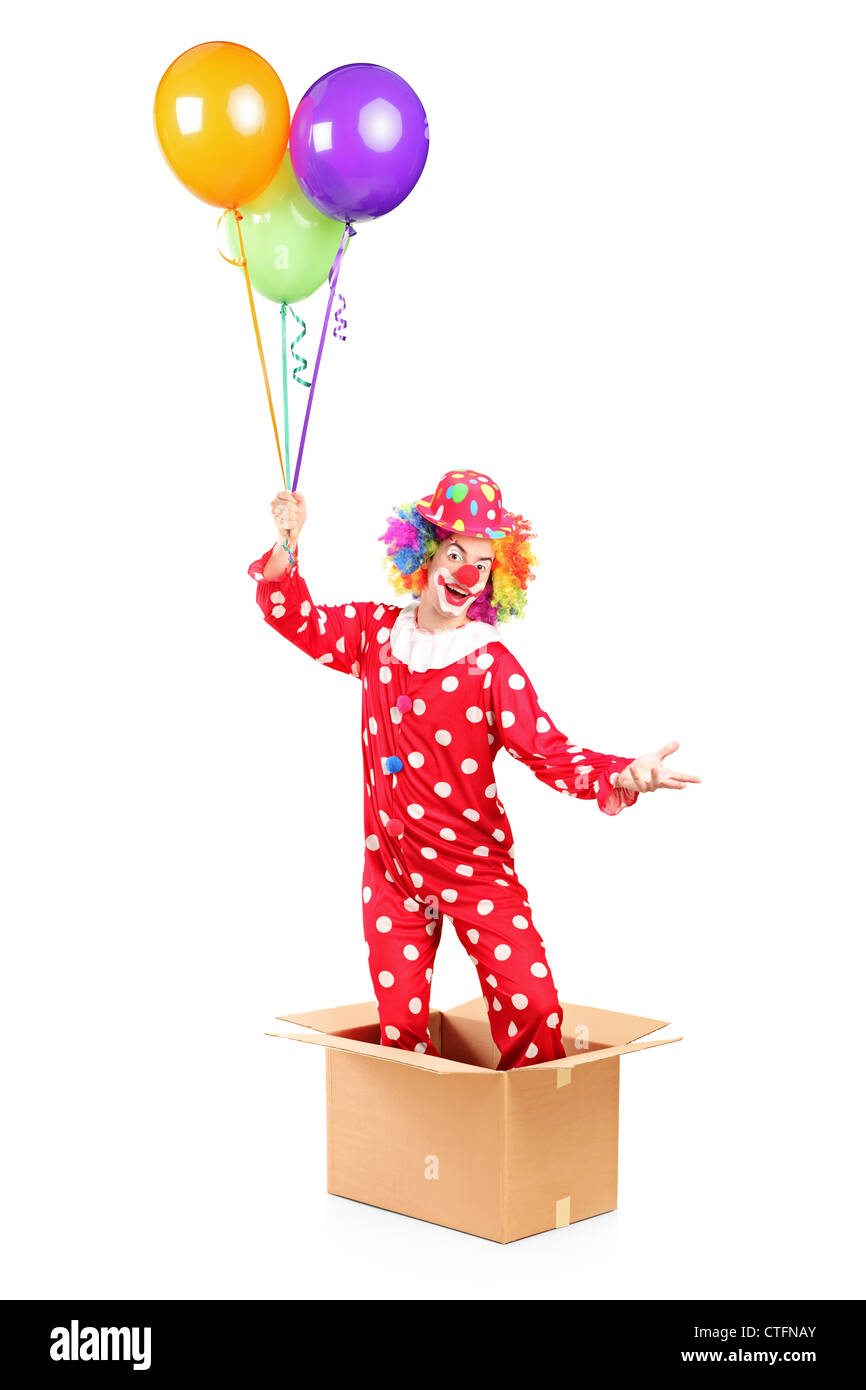 Clown holding balloons and standing in a cardboard box, isolated on white background - Stock Image