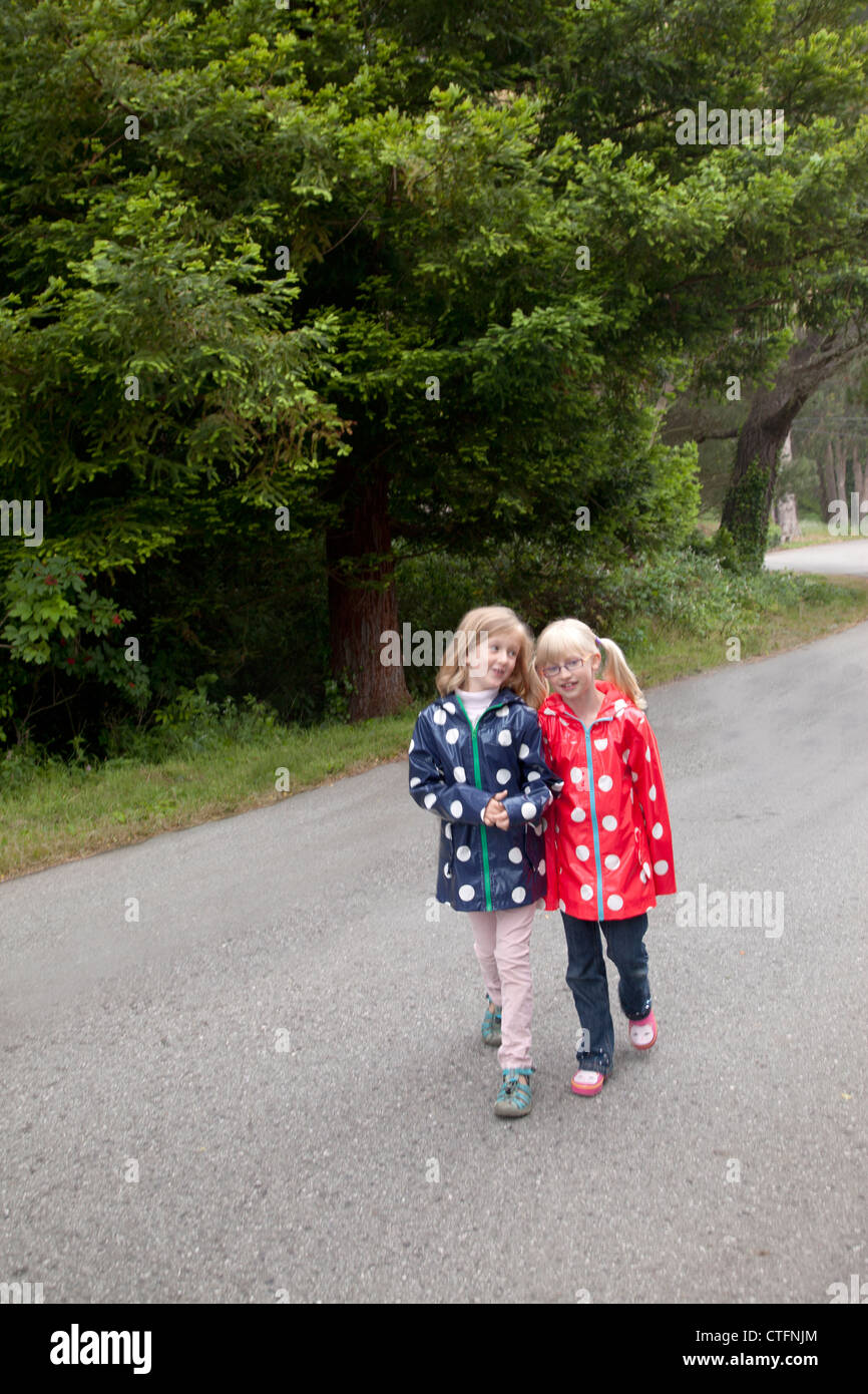 Two young friends together both wearing polka dotted raincoats. - Stock Image