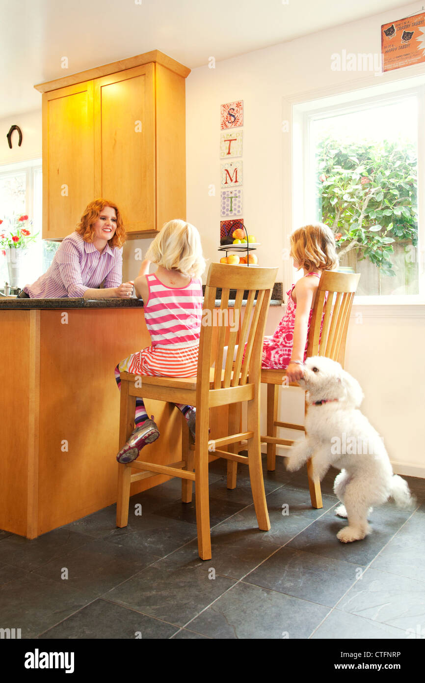 A mother and two daughters are in the kitchen, one daughter is feeding the dog. - Stock Image