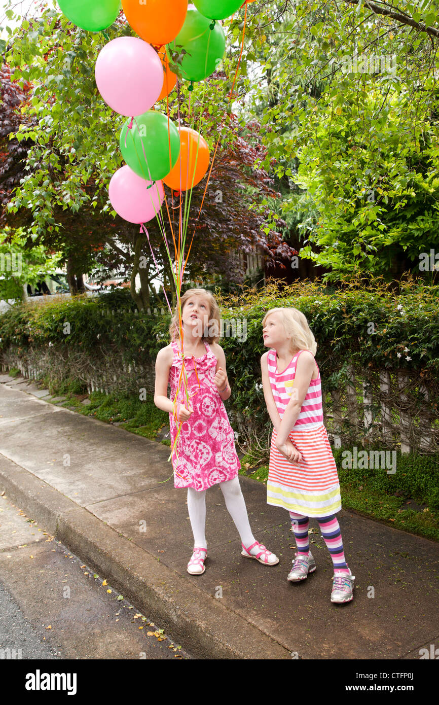 Two girls are on the street holding colorful balloons. - Stock Image