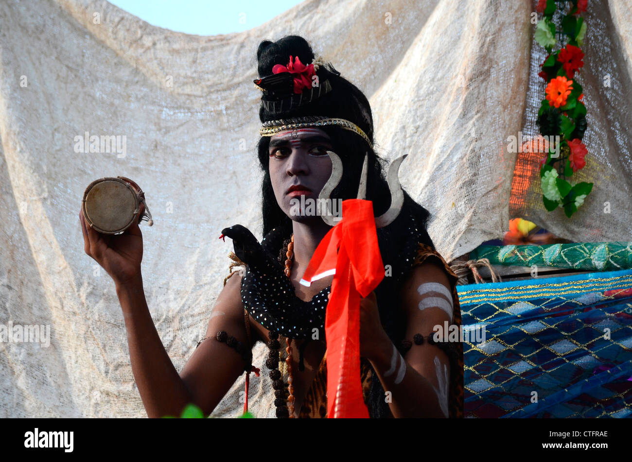 A man posing as Lord Shiva in a float - Stock Image