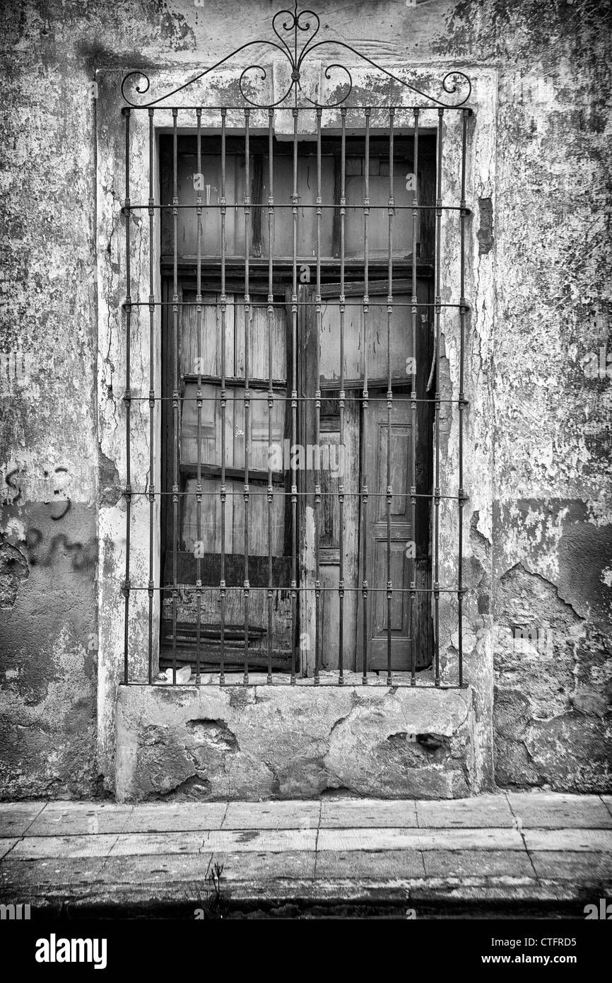 Window with closed shutter and metal grill. - Stock Image