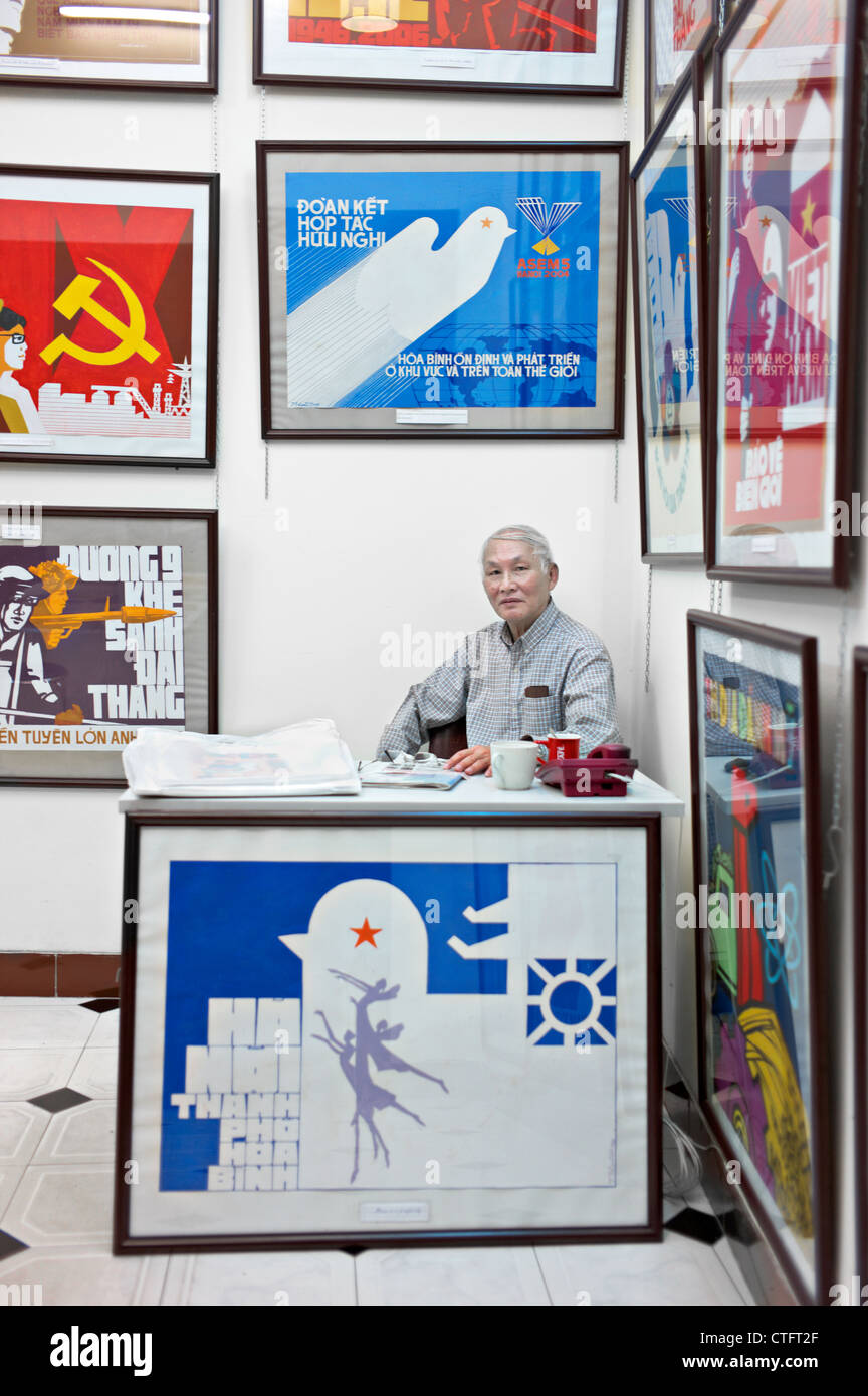 A propaganda poster shop in Vietnam with a man sitting behind a desk. - Stock Image