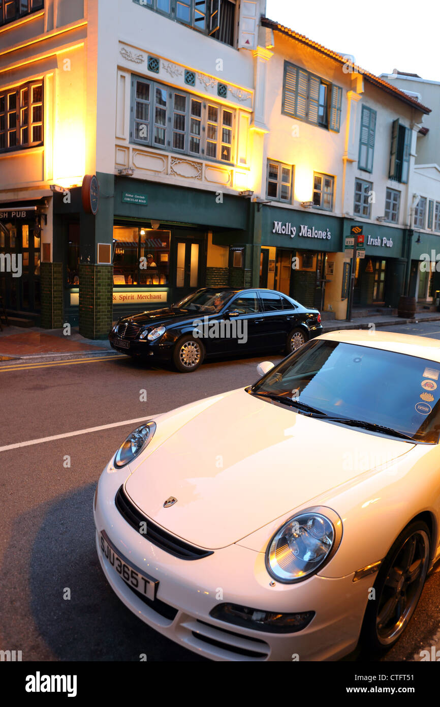 Luxury cars parked outside Molly Malone's bar near Boat Quay in Singapore. - Stock Image
