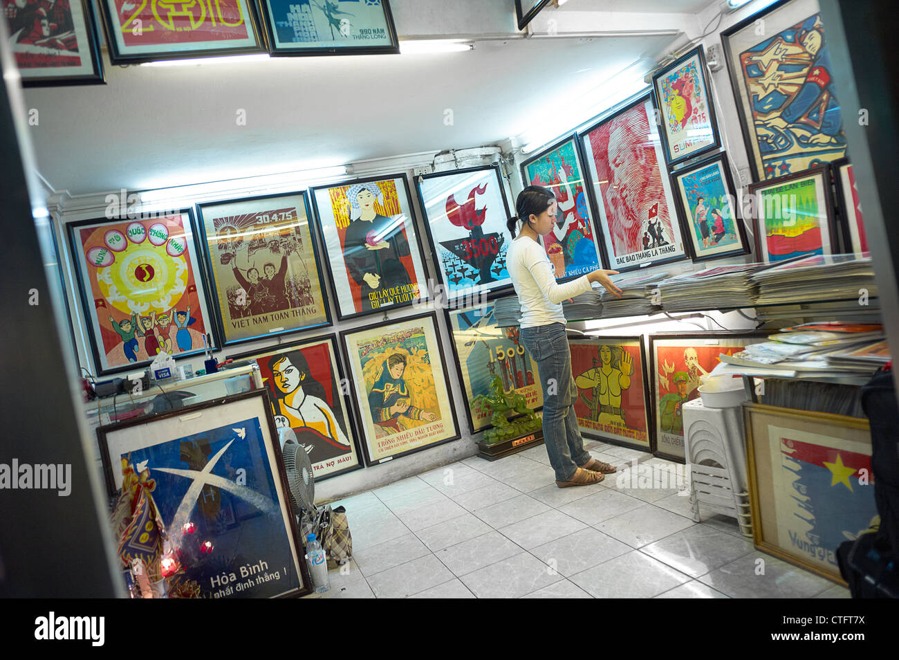 A two-story propaganda poster shop in Vietnam with people browsing through the posters. Stock Photo