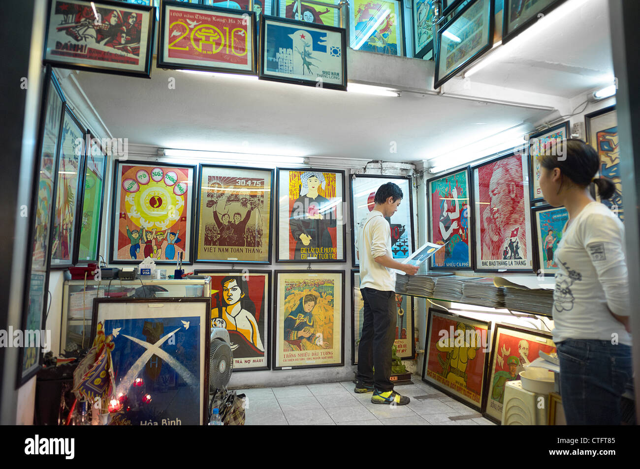 A two-story propaganda poster shop in Vietnam with people browsing through the posters. - Stock Image