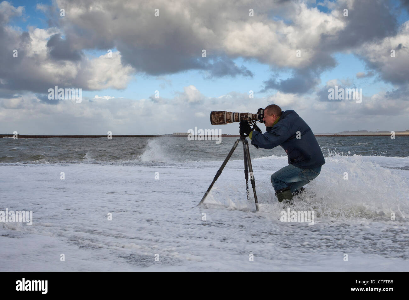 The Netherlands, IJmuiden, Photographer Frans Lemmens on pier during storm. - Stock Image