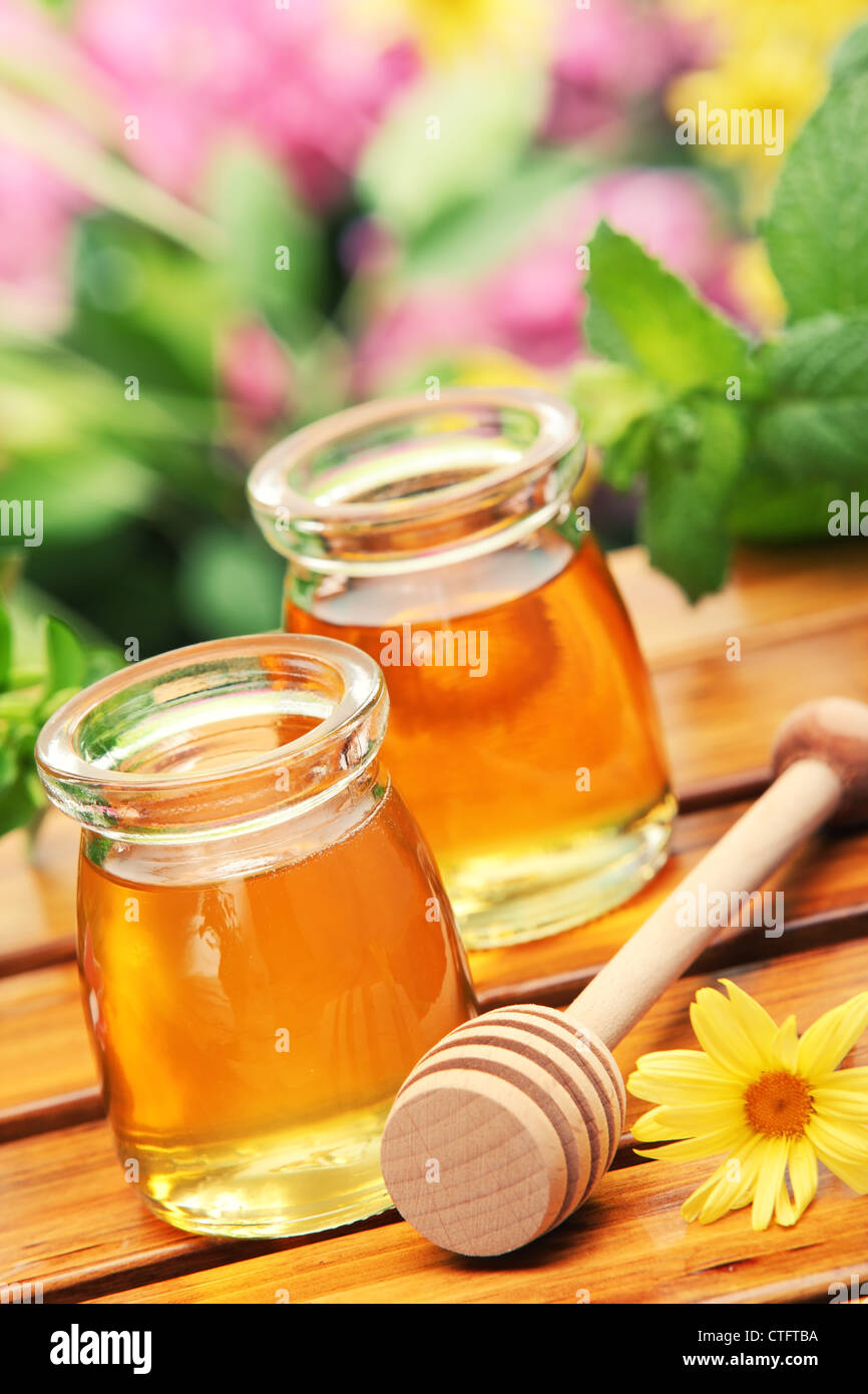 Honey in glass jars with flowers background. Stock Photo